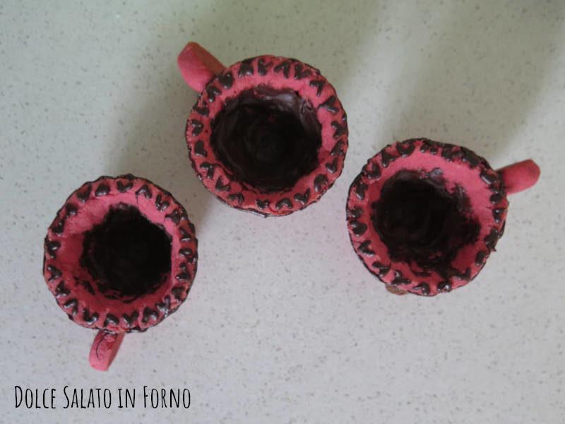 Foderare le tazze di frolla con del cioccolato fondente fuso